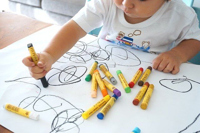 Toddler using markers to draw on a white sheet of paper