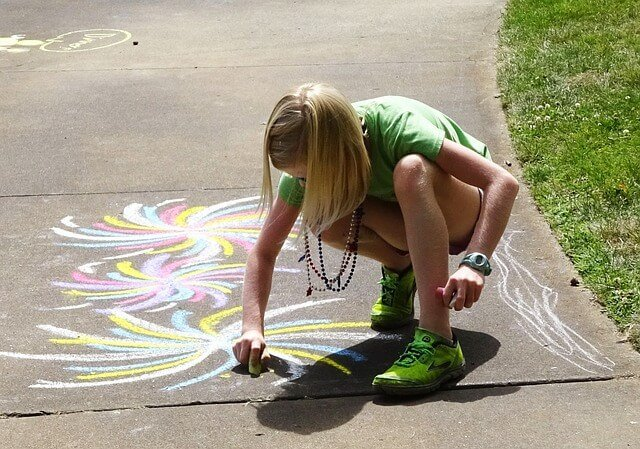 Girl drawing on asphalt with colored chalk