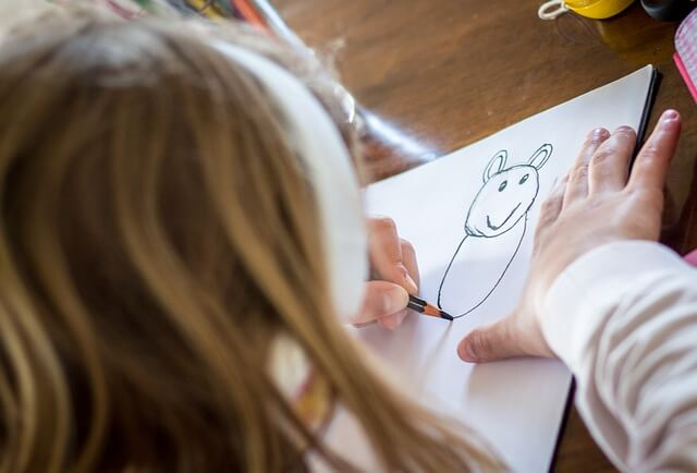Close-up of paper on which a girl is drawing an animal. Using a drawing prompt for kids can help kids express themselves.