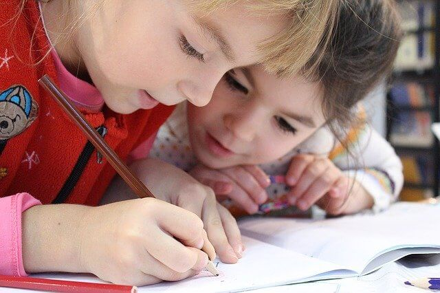Two girls drawing together with pencils using drawing prompts for kids