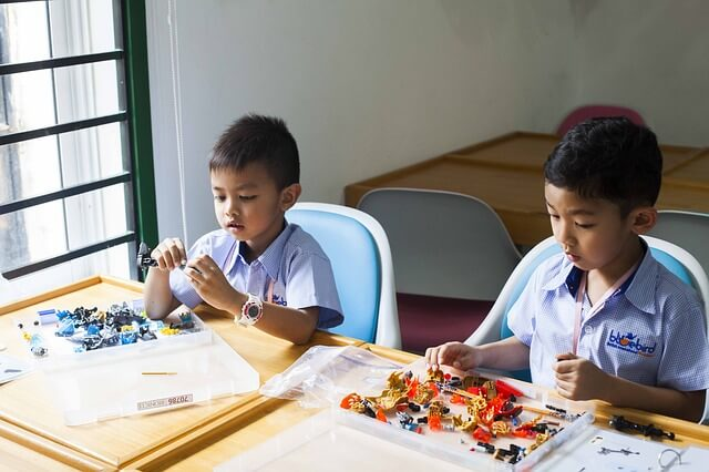Two school kids playing with construction toys