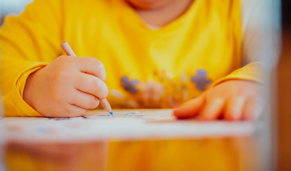 Close-up of a child drawing with a pencil